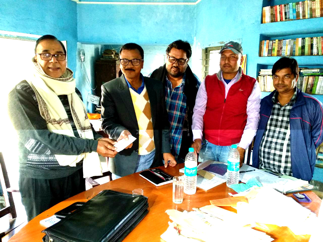 Dr.Madhepuri receiving a receipt from DEO Shri Ugrace Prasad Mandal for his Library Development act of philanthropy in presence of Secretary and other members