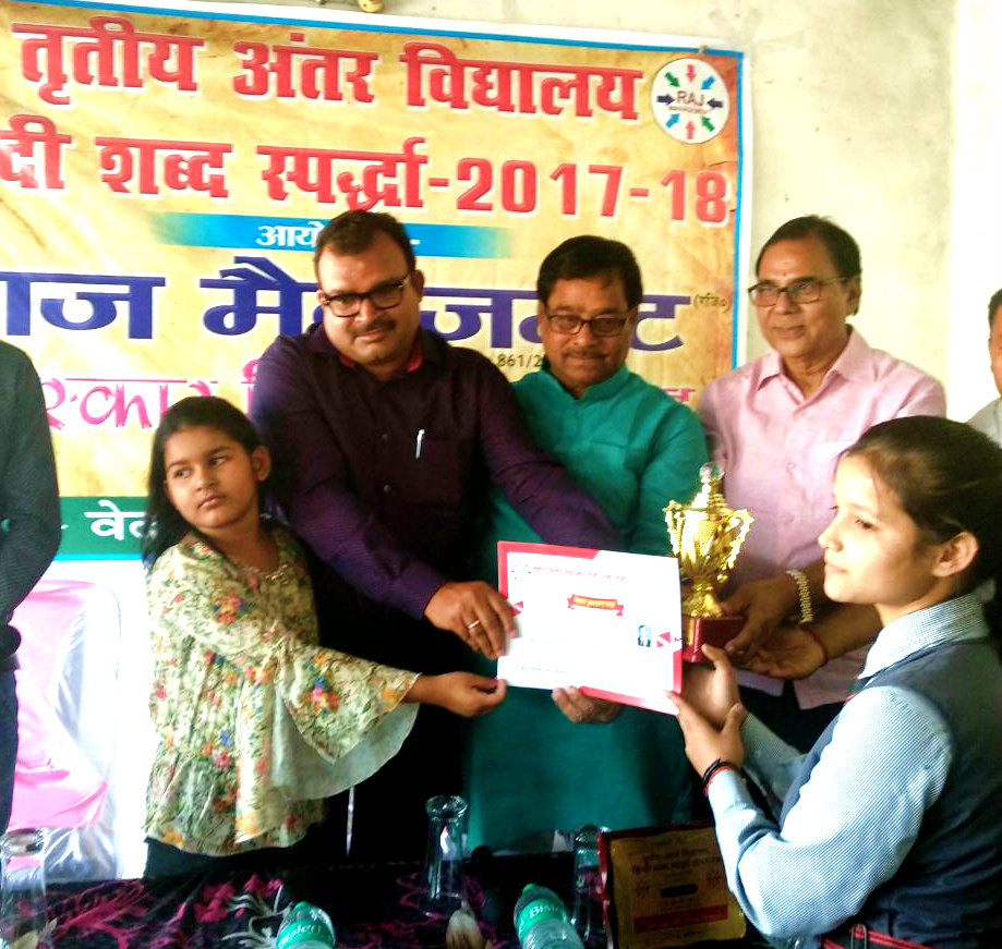 Educationist Dr.Bhupendra Madhepuri, Chairman Dr.K.P.Yadav, Chief Guest Shri Sanjay Kumar Nirala with Baby Palak giving momento & certificate to a winning scholar in 3rd Inter School Hindi Word Championship 2017-18 at Madhepura.