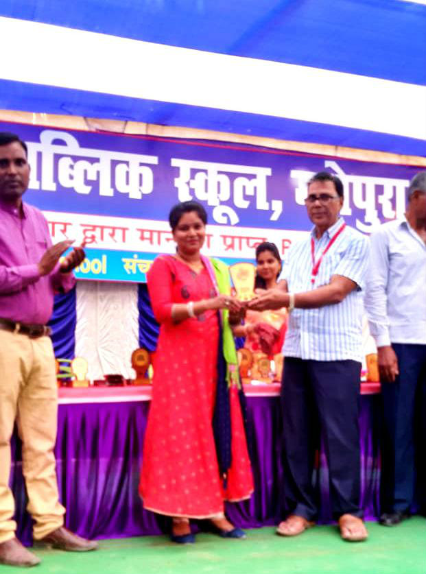 A dedicated teacher receiving momentos by the Chief Guest Dr.B.N.Yadav Madhepuri for her superb behavior with students & guardians of Tulsi Public School.